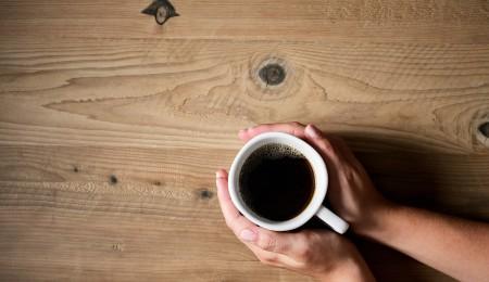 Hands holding white coffee mug